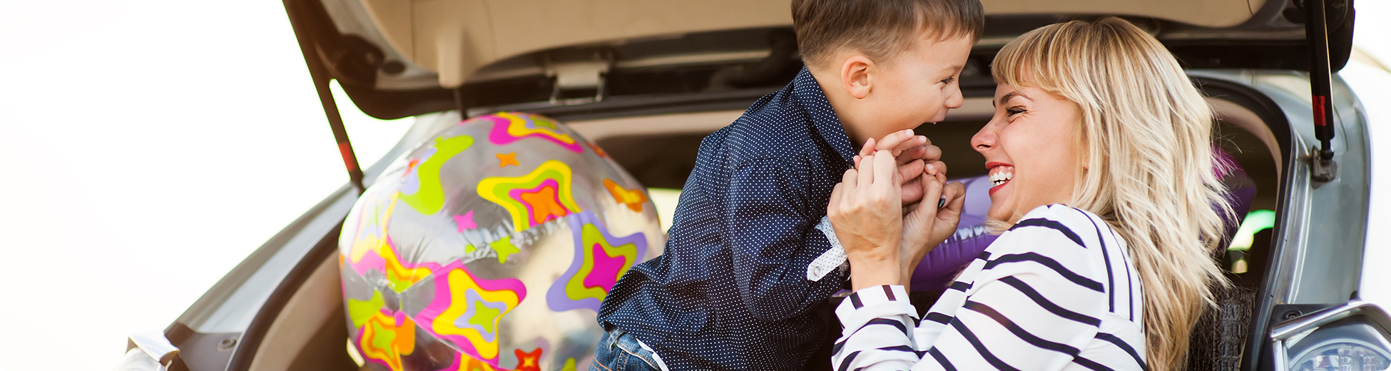 Women and son embracing in front of new car