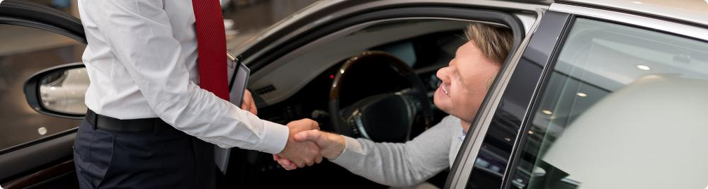 customer shakes car dealer hand